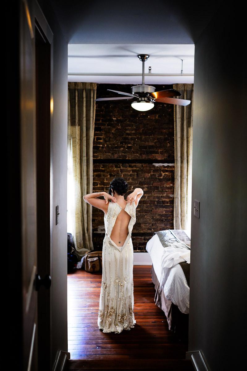 Bride puts on her dress at Restoration Hotel Charleston.