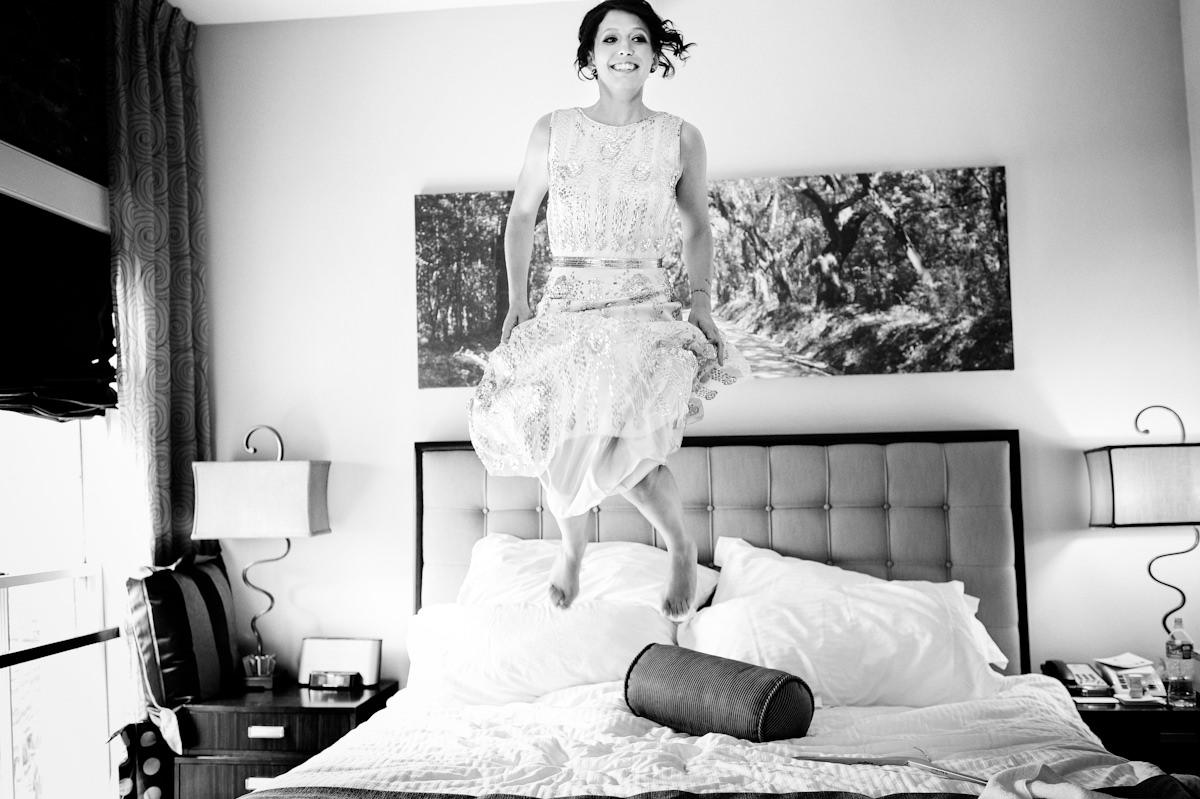 Bride jumps on bed at Restoration Hotel Charleston.