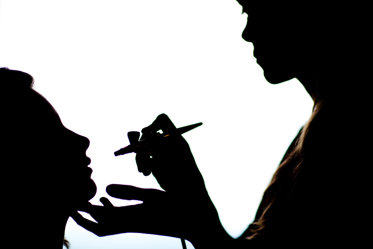 Silhouette of bride's make-up being applied
