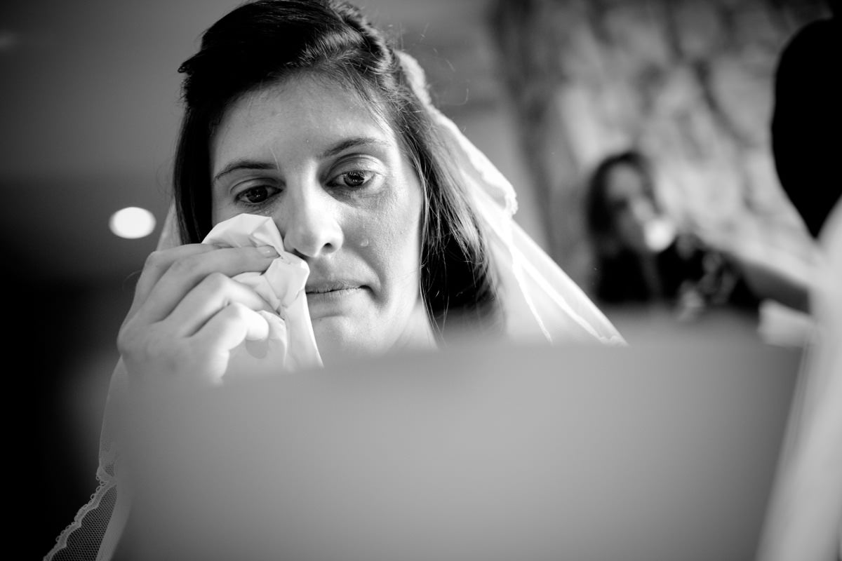 Bride wipes away tears as she reads card from bridegroom