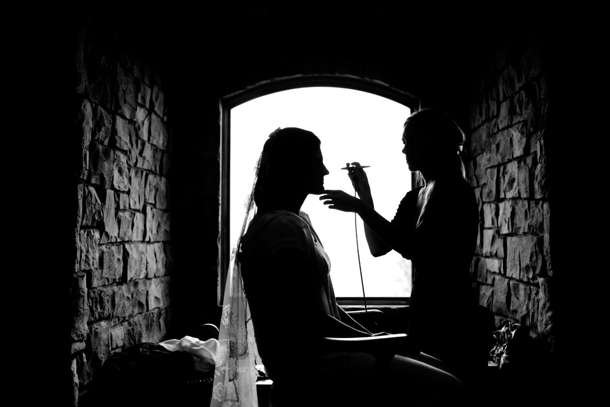 Silhouette photo of bride's make-up being applied