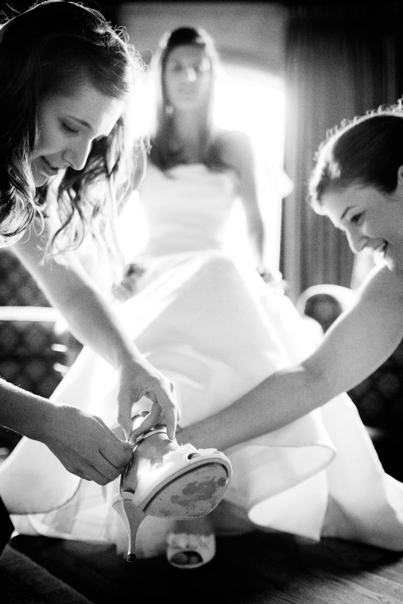 Bridesmaids help bride with her shoes in Linville, North Carolina wedding