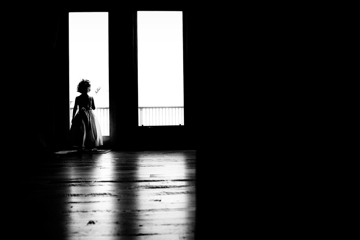 Flower girl staring out of the window in Linville wedding