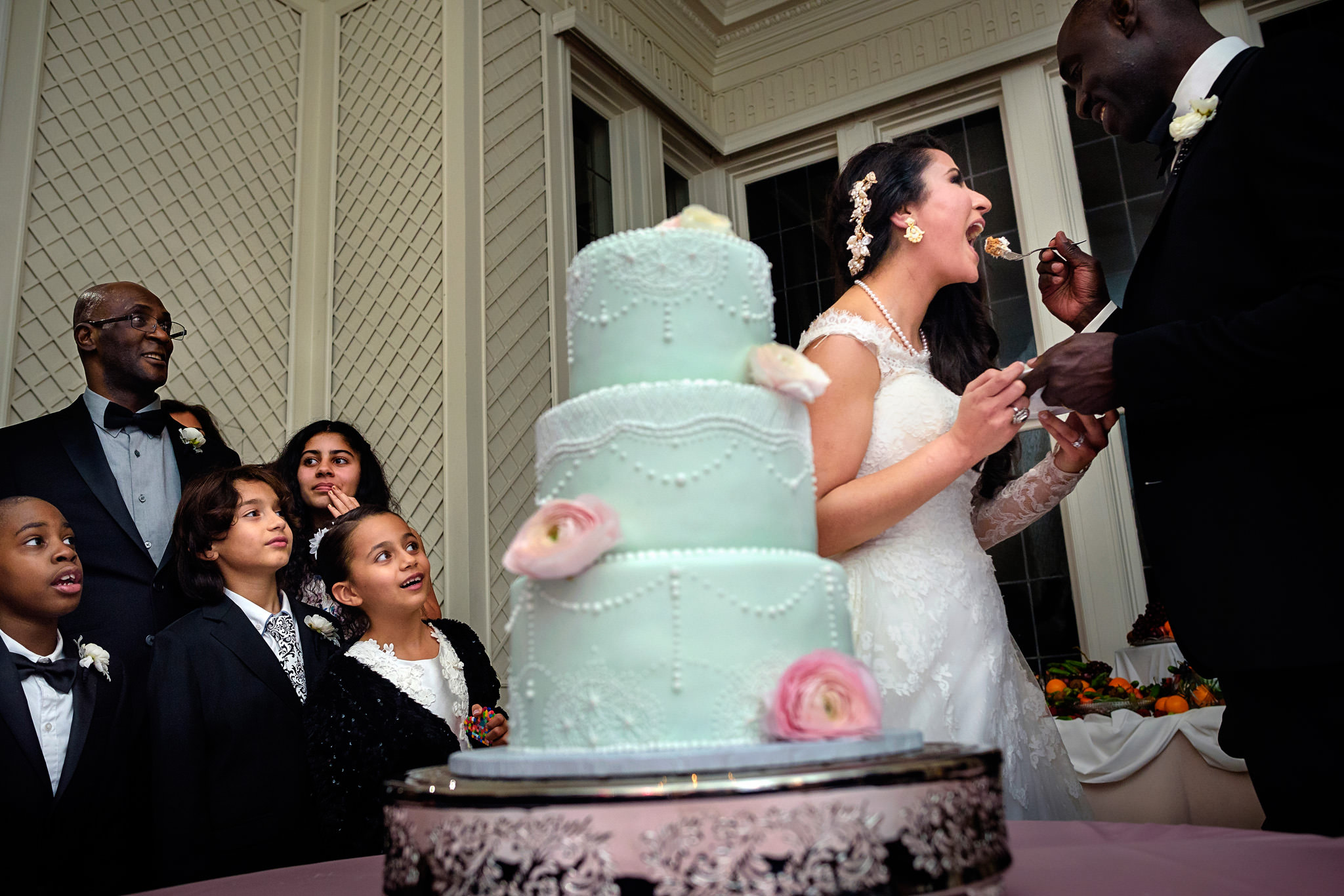 Bridegroom feeds bride wedding cake