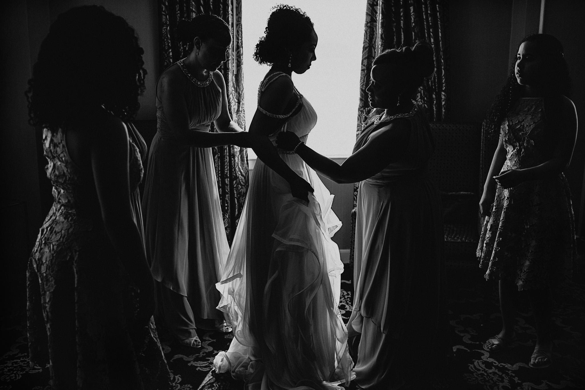 Bridesmaids help bride with her wedding dress