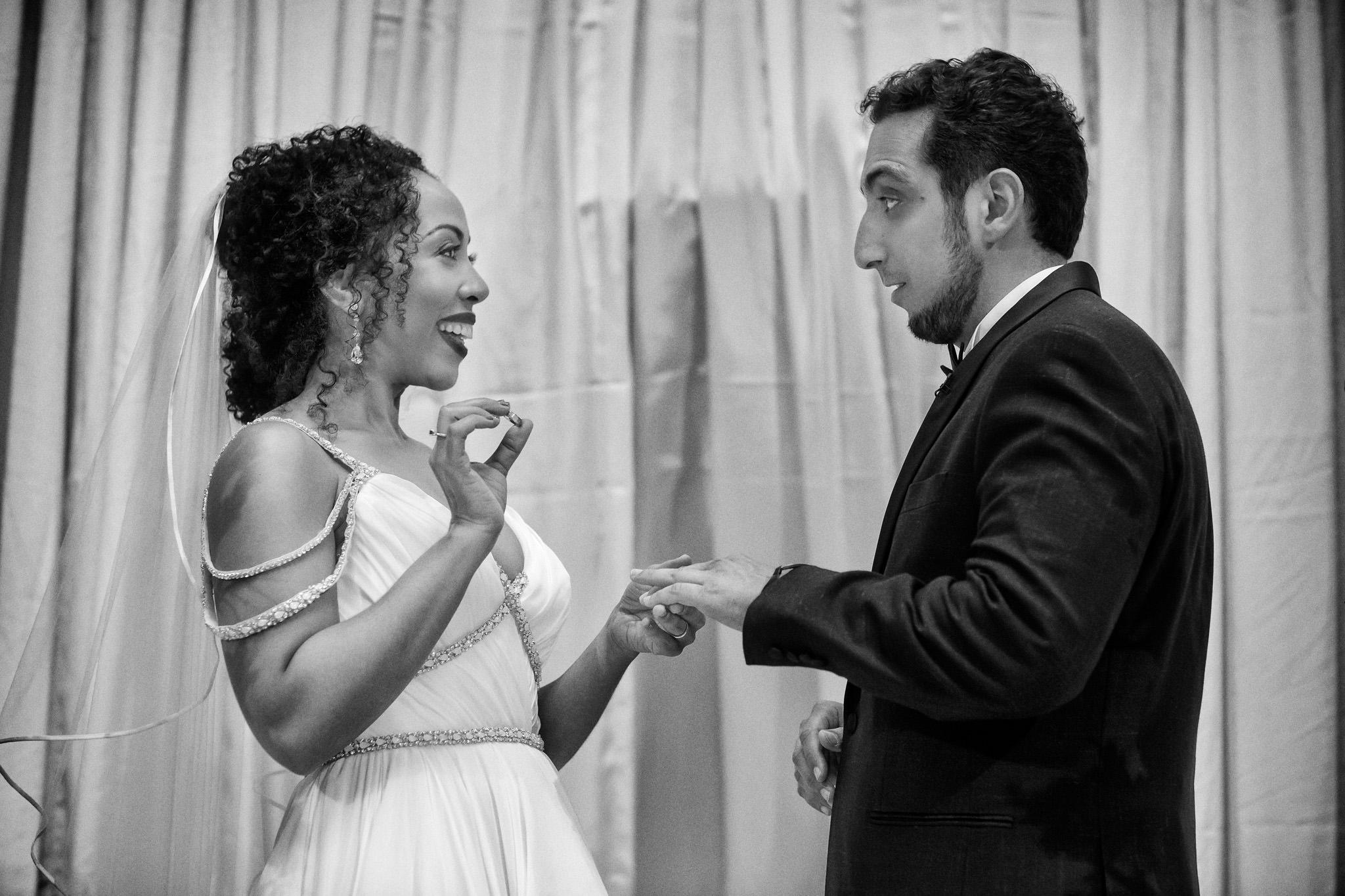 Bride and bridegroom exchange wedding rings at wedding ceremony at the San Francisco Design Center in San Francisco