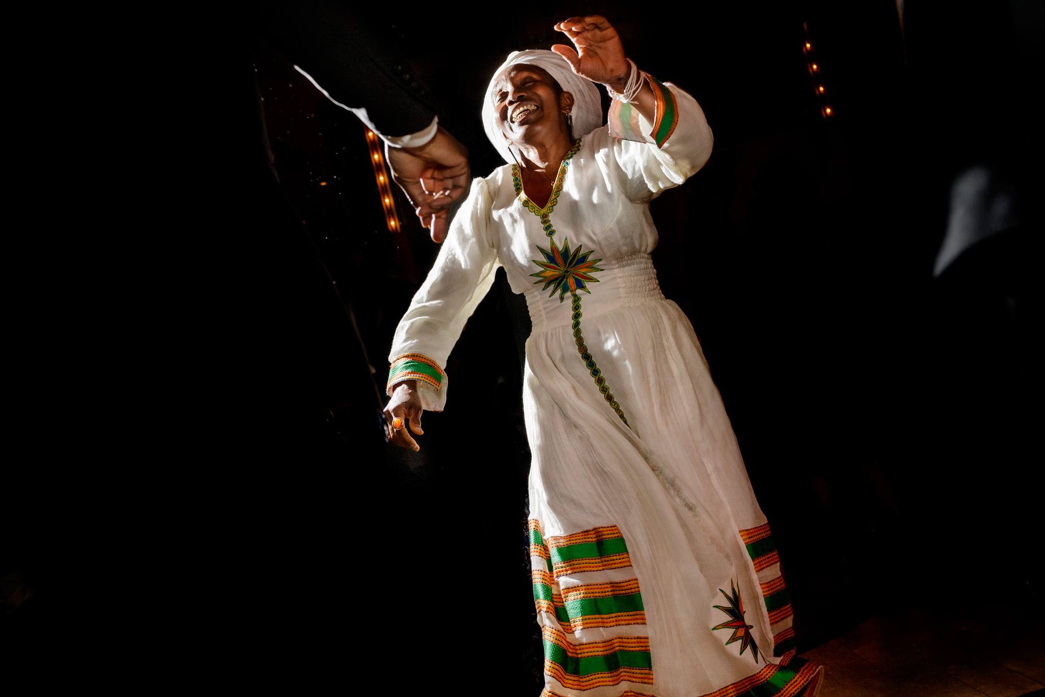 African-american wedding guest dances in traditional African dress at